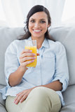 Cheerful brunette offering orange juice to camera