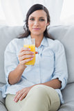 Peaceful brunette offering orange juice to camera