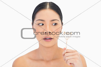 Apprehensive natural model holding eyelash curler