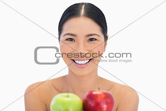 Smiling brunette holding red and green apples