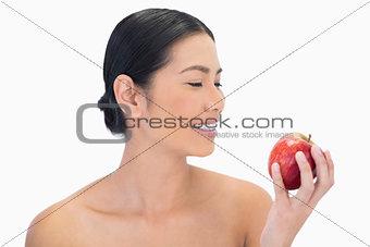Smiling black haired model having red apple