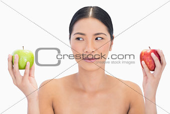 Black haired model holding apples in both hands looking at the green one