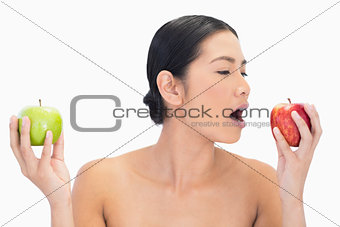 Black haired model holding apples in both hands eating the red one