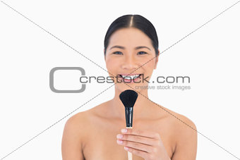 Smiling beautiful model holding powder brush