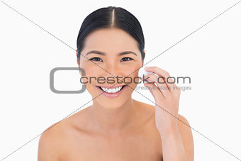 Smiling beautiful model using cotton pad on her face