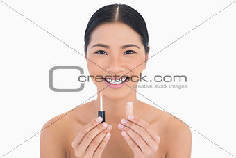Smiling beautiful model holding lip gloss