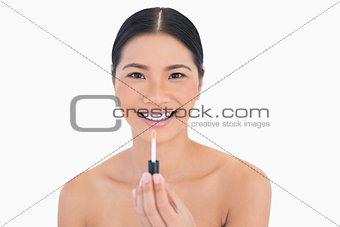 Smiling attractive model holding lip gloss