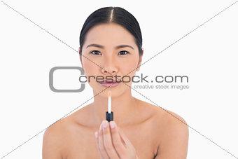 Calm attractive model holding lip gloss