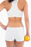 Back of female slender body in shorts holding orange in right hand
