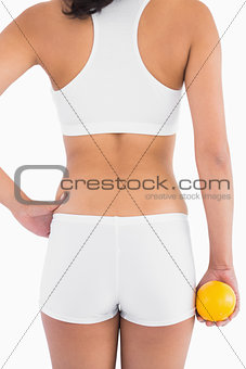 Back of female slender body in shorts holding orange in right hand