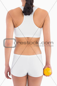 Female slender body in white sport underwear holding orange