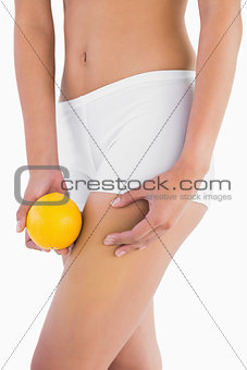 Slender woman squeezing fat on thigh as she holds orange
