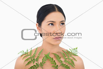 Thoughtful sensual dark haired model posing with fern