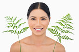 Cheerful sensual dark haired model posing with fern