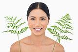 Cheerful sensual dark haired model posing with fern