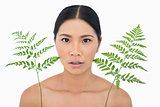 Surprised sensual dark haired model with fern looking up