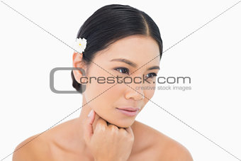 Thoughtful sensual model with white flower in her hair