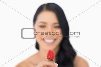 Attractive brown haired model holding strawberry