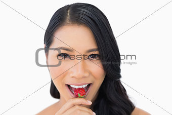 Attractive brown haired model eating strawberry