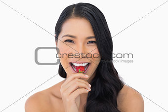 Smiling attractive brown haired model eating strawberry