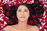 Pensive sensual dark haired model lying in rose petals