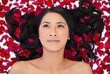 Pensive sensual dark haired model lying in rose petals