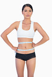 Self confident slim woman measuring her waist