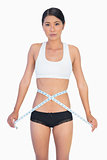 Serious slim woman measuring her waist