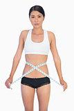 Serious slim woman measuring her waist