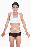Cheerful slim woman measuring her waist