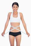 Cheerful slim woman measuring her waist