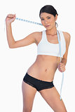 Self confident slim woman holding her measuring tape