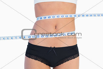 Slim belly surrounded by measuring tape