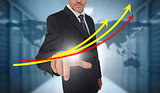 Businessman touching red and yellow growth lines with world map on background