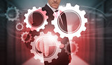 Businessman selecting futuristic cog and wheel interface