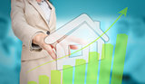 Businesswoman touching futuristic house interface with green bar chart