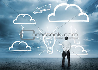 Businessman considering cloud computing graphics with light bulb