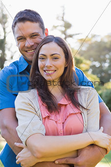 Attractive couple smiling at the camera and hugging