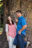 Smiling couple leaning on a tree