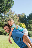 Daughter getting piggy back from dad smiling at camera