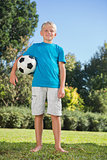 Young blonde boy holding football