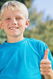 Little blonde boy smiling at camera giving thumbs up