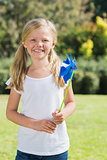 Blonde girl smiling and holding pinwheel
