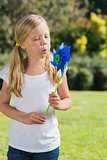 Young blonde girl blowing pinwheel