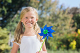 Young blonde girl holding pinwheel smiling at camera