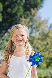 Cute blonde girl holding pinwheel smiling at camera