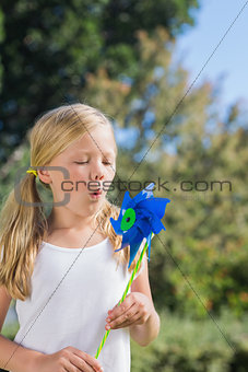 Small child blowing the pinwheel