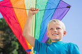 Child raising his arm with a kite in it