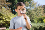 Cute boy looking through a magnifying glass