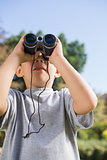 Boy looking through binoculars to the sky